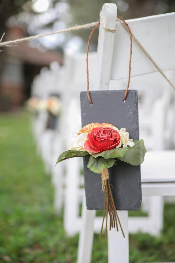 在空白婚礼椅子的花 免版税库存照片