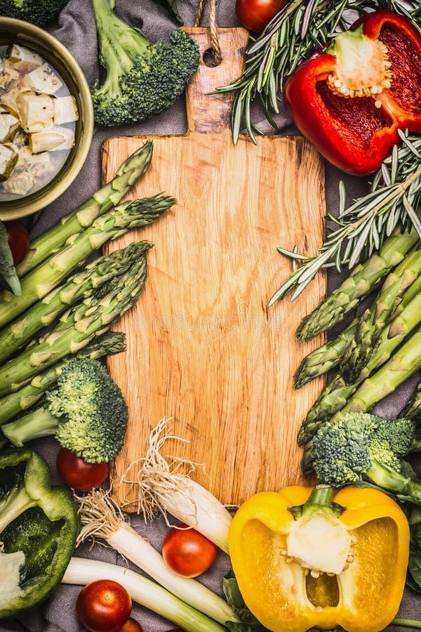 在空白的木切板,顶视图附近的芦笋和菜成份 免版税库存图片