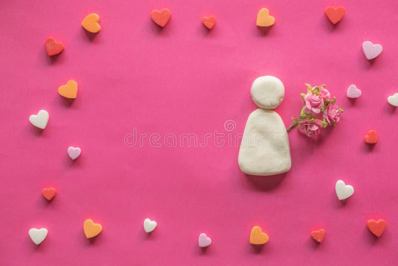 在空白的桃红色背景和象动画片妇女有桃红色花的,爱象,情人节附近的许多心脏 库存图片