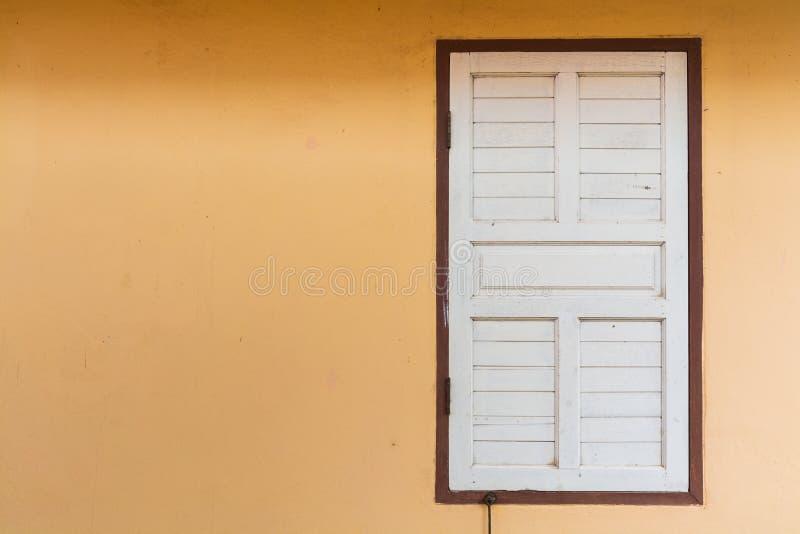 在空白的桔子被绘的水泥墙壁上的白色老木窗口 免版税库存照片