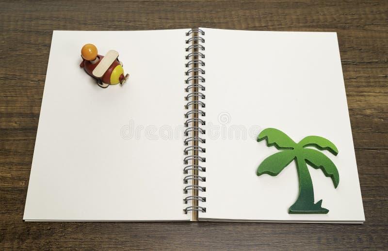 在空白的白色笔记本的红色和黄色木飞机有绿色棕榈树的 库存图片