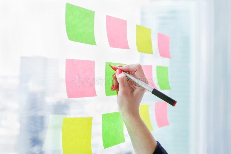 在空白的稠粘的笔记的妇女文字关于窗口在办公室 免版税库存照片