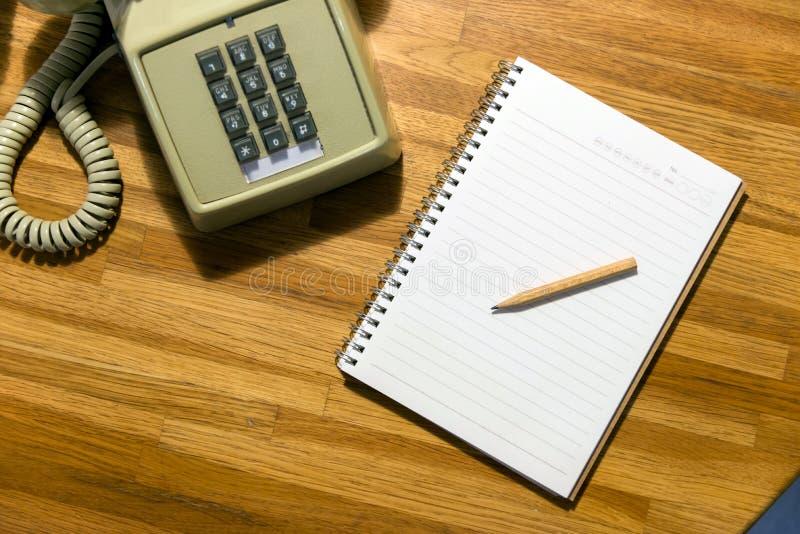 在空白的笔记本的小铅笔有葡萄酒拨号电话的 图库摄影