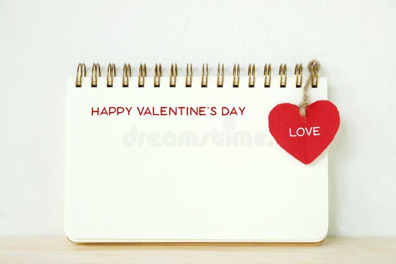 在空白的笔记本的愉快的情人节词与垂悬的红色 免版税库存图片