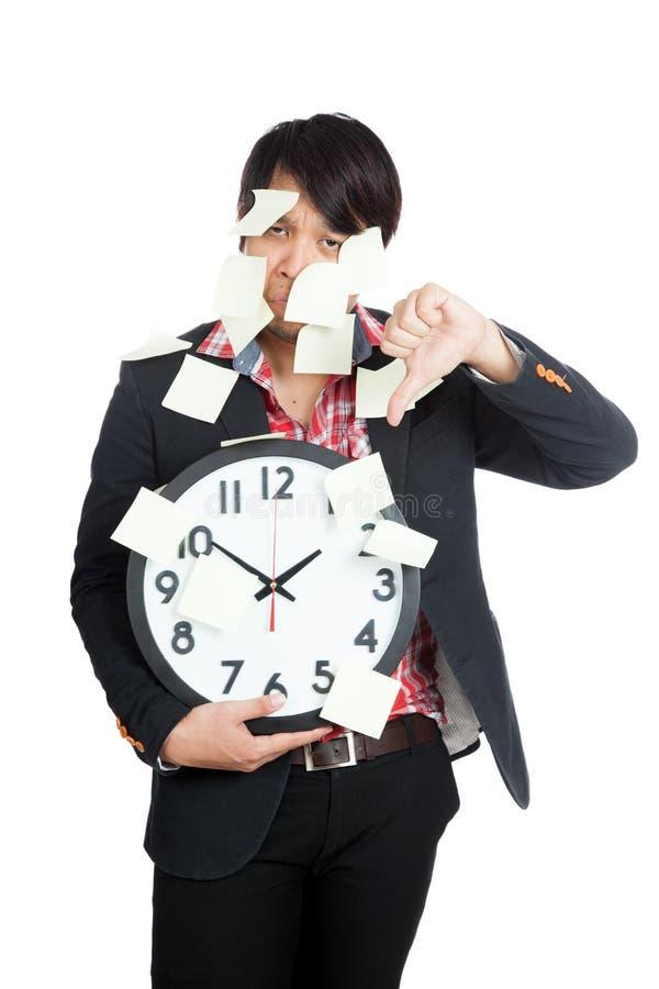 在空白的笔记盖的亚洲办公室人举行时钟用拇指 免版税库存照片