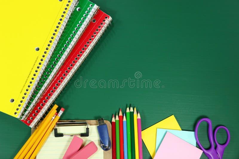 在空白的黑板的学校用品 免版税库存图片