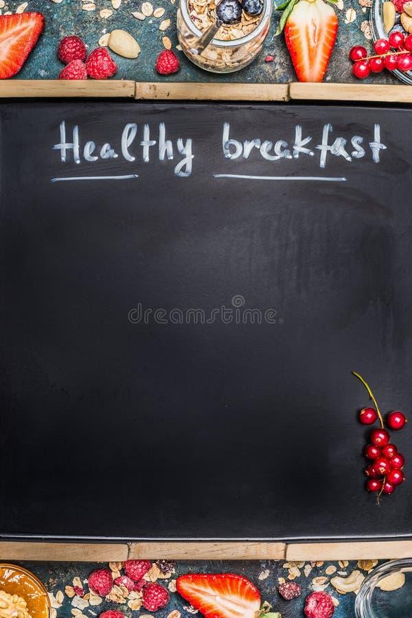 在空白的黑黑板背景的题字健康早餐 健康早餐用莓果、muesli和坚果,框架 库存图片