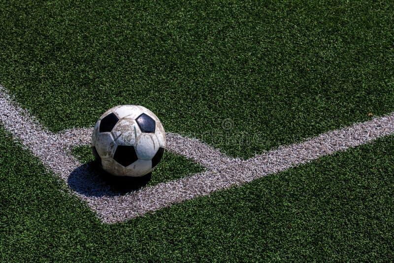 在空白线路的老足球橄榄球在人为草皮 库存图片