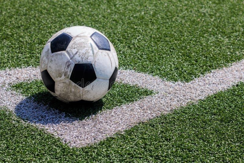 在空白线路的老足球橄榄球在人为草皮 库存照片