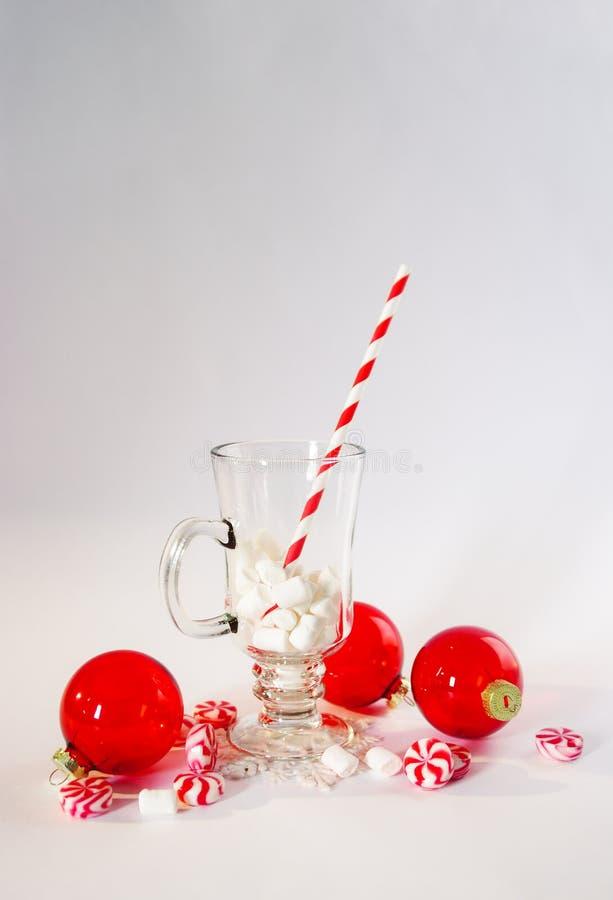 在空白背景的圣诞节装饰 红色球装饰品和糖果 有蛋白软糖和有斑纹的纸秸杆的杯 免版税库存照片