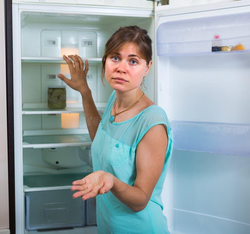 在空的冰箱附近的妇女 免版税库存图片