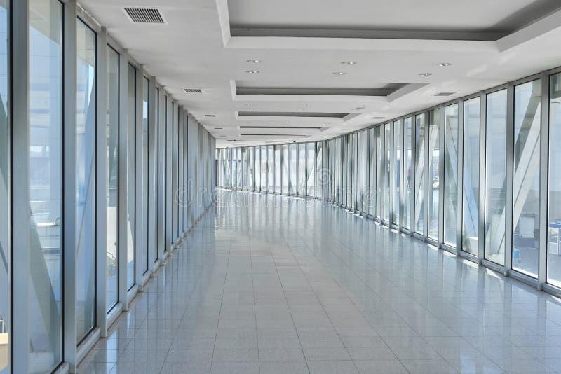 在空的办公室大厅的全景有玻璃墙窗口的 做金属和玻璃 现代走廊金属和玻璃建筑 免版税库存照片