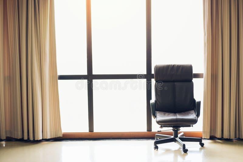 在空的办公室空间的布朗行政皮椅与大窗口和装饰 免版税库存图片