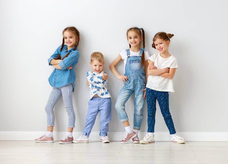 在空的墙壁附近的愉快的孩子朋友 免版税库存图片