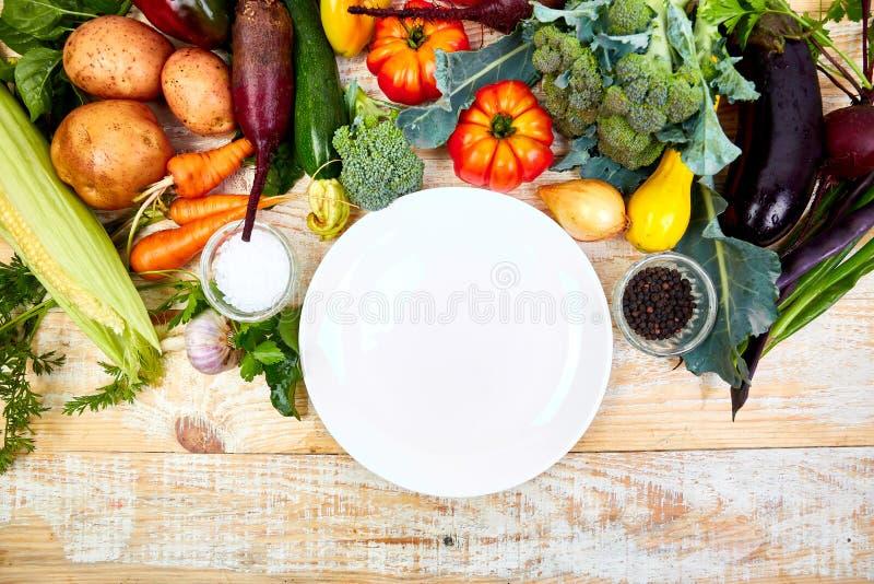 在空的板材附近的各种各样的有机蔬菜成份 库存图片
