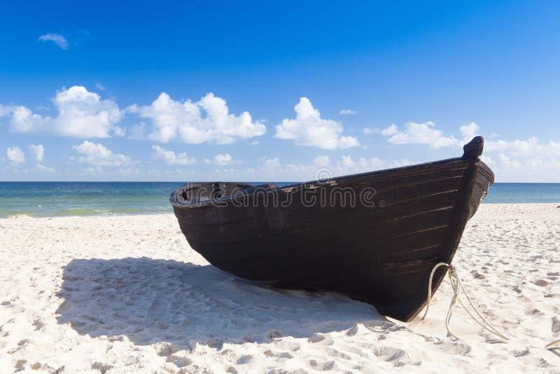 在空的海滩的老木渔船 免版税图库摄影