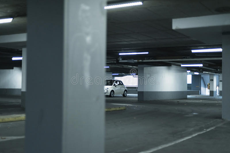 在空的车库停放的小白色汽车 免版税库存照片