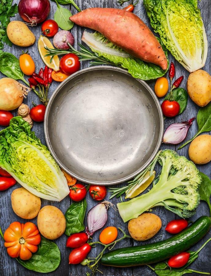 在空的钢板附近的新鲜的五颜六色的有机季节菜成份在土气木背景,顶视图,拷贝空间 免版税库存图片