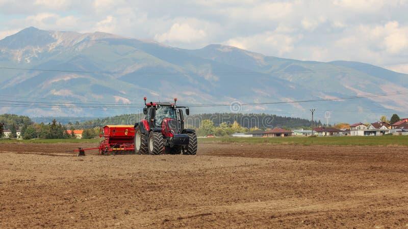 在空的领域、村庄房子和山的拖拉机播种在背景中 免版税库存照片
