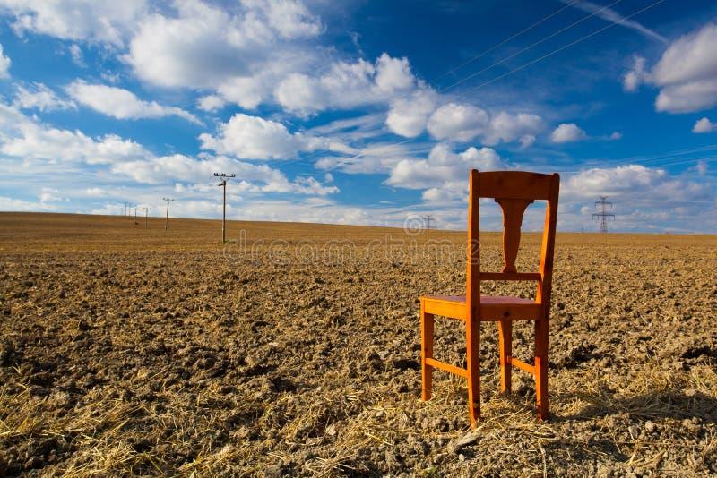 在空的领域的老木椅子 免版税库存照片