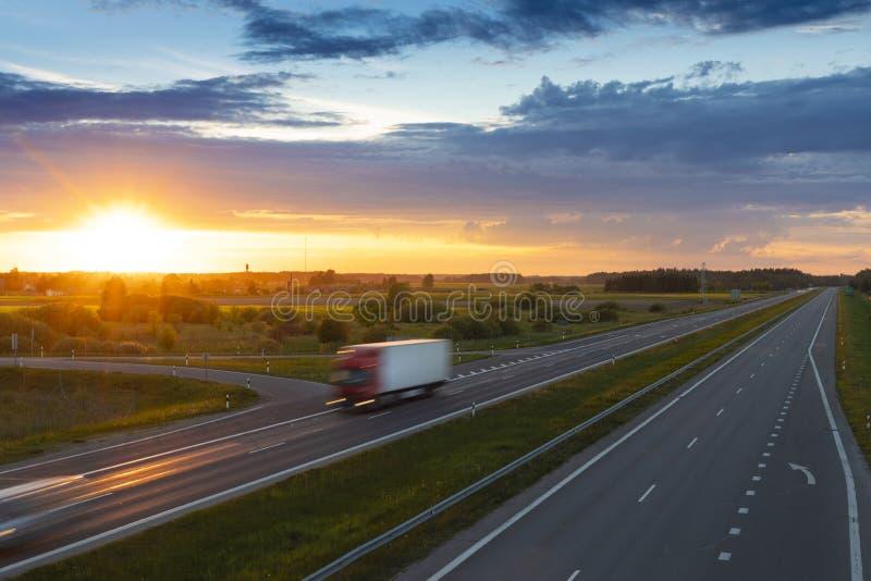 在空的高速公路的货物卡车在美好的夏天晚上日落 免版税库存照片