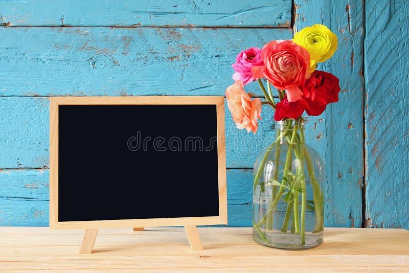 在空的黑板旁边的花,在木桌上 复制空间 库存图片