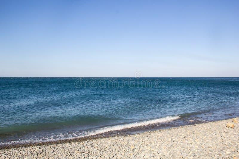 在空的Pebble海滩的海泡沫似的波浪 免版税库存图片