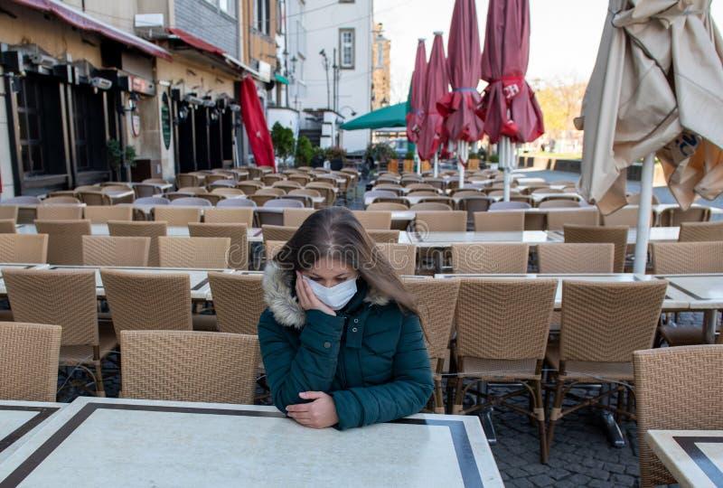 在空荡荡的咖啡馆里戴医用口罩的女人 库存照片