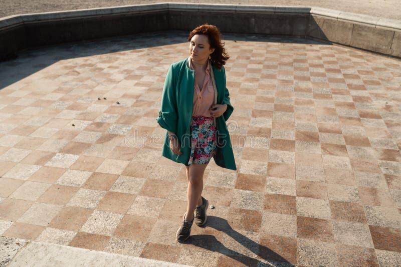 在穿着一条五颜六色的裙子的一个空的喷泉的愉快的年轻女人跳舞 免版税库存照片