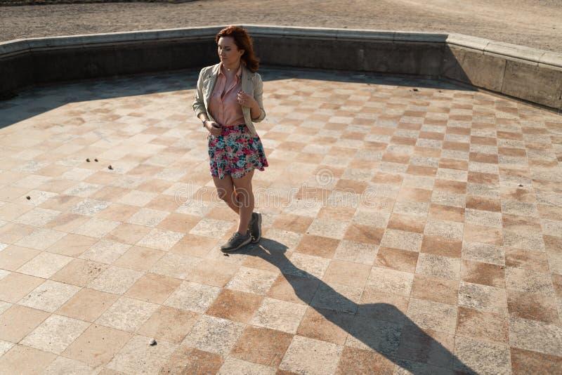 在穿着一条五颜六色的裙子的一个空的喷泉的愉快的年轻女人跳舞 免版税库存图片