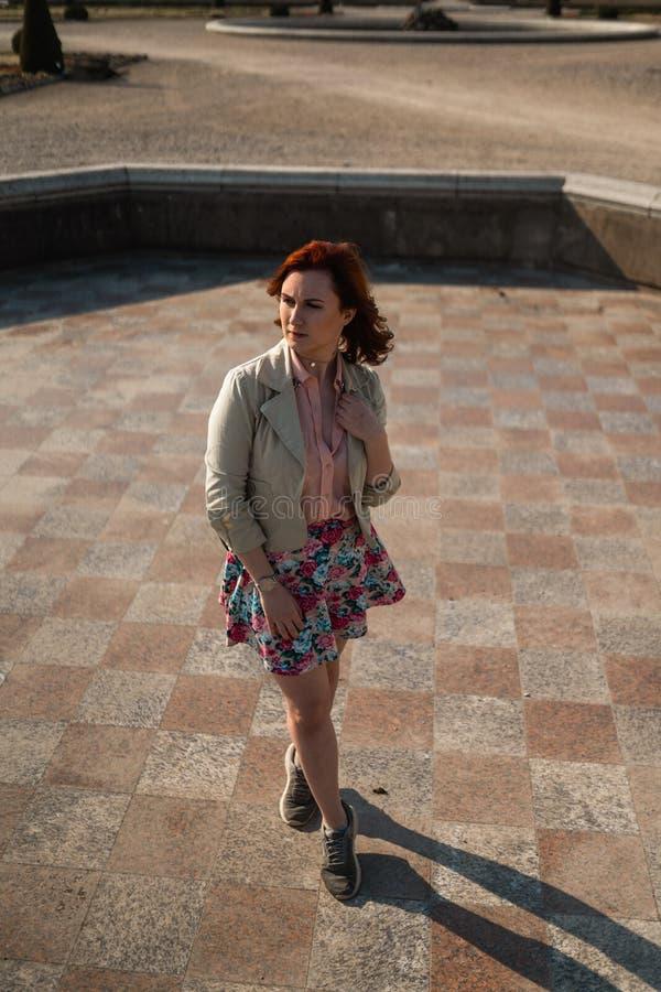 在穿着一条五颜六色的裙子的一个空的喷泉的愉快的年轻女人跳舞 图库摄影
