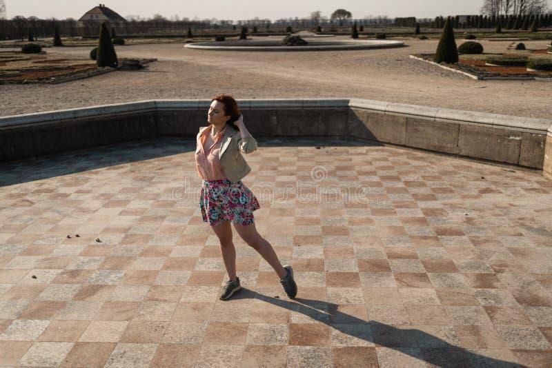 在穿着一条五颜六色的裙子的一个空的喷泉的愉快的年轻女人跳舞 库存图片