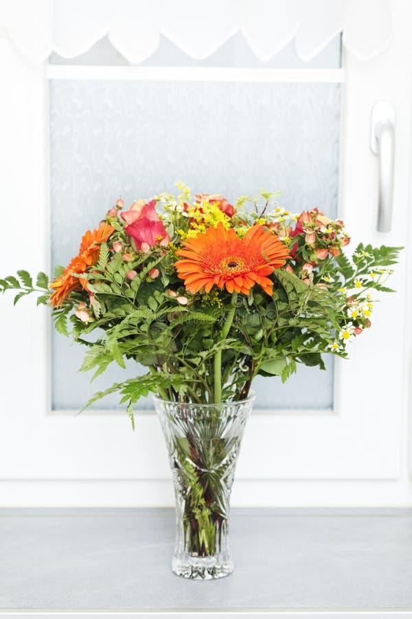 在窗前的花瓶里放着橙色、黄色和红色的花束……一束橙色、黄色和红色的花在窗前的花瓶里,在å 库存图片