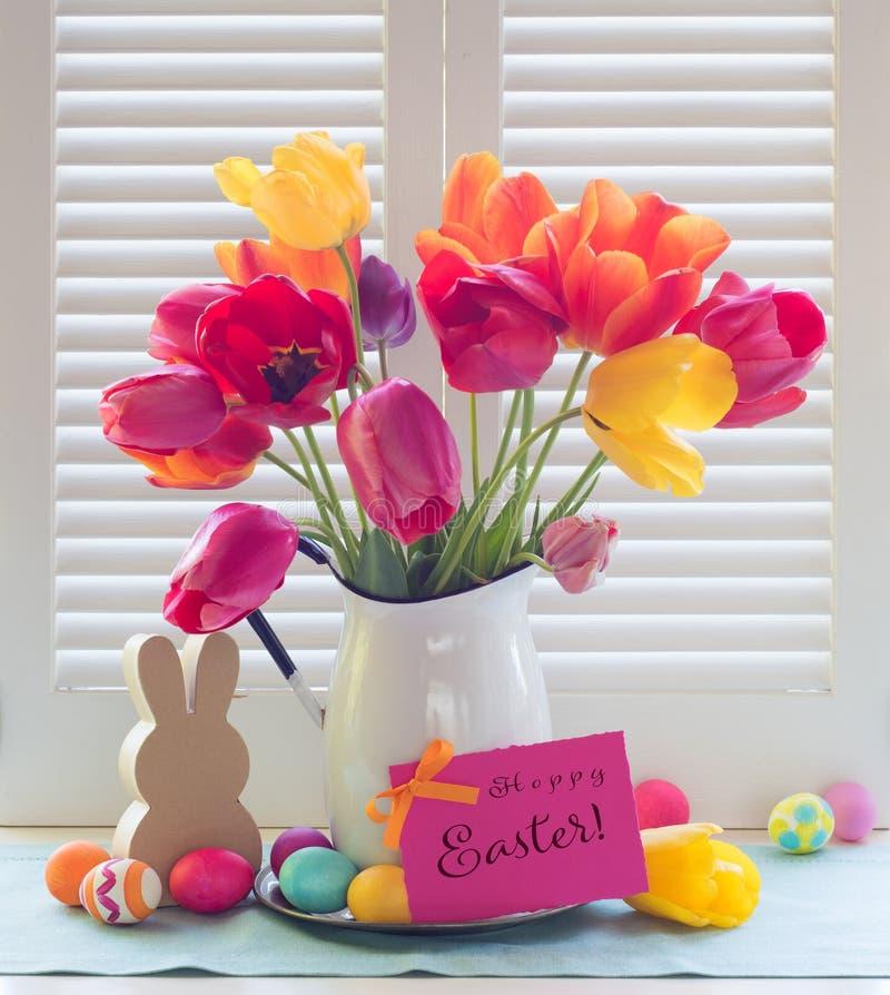 在窗口光的五颜六色的复活节彩蛋和郁金香花束静物画与跳跃的步子的复活节卡片 库存照片
