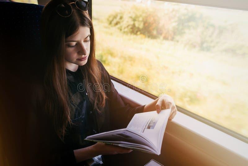 在窗口光的时髦的行家女孩阅读书在火车 Trav 免版税库存照片