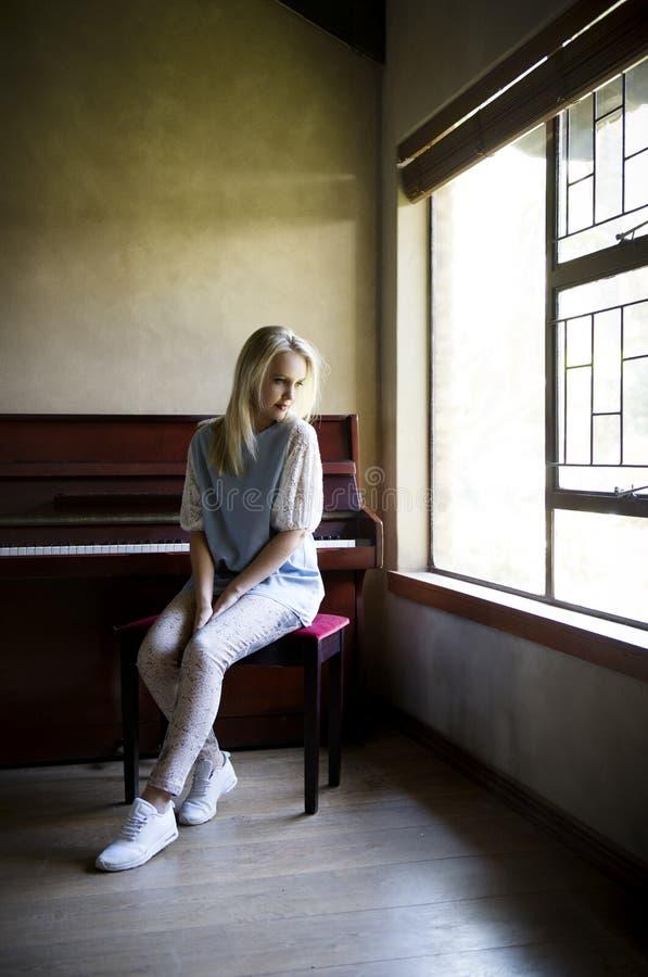 在窗口前面的钢琴安装的作白日梦的白肤金发的妇女与放出的自然光  免版税库存照片