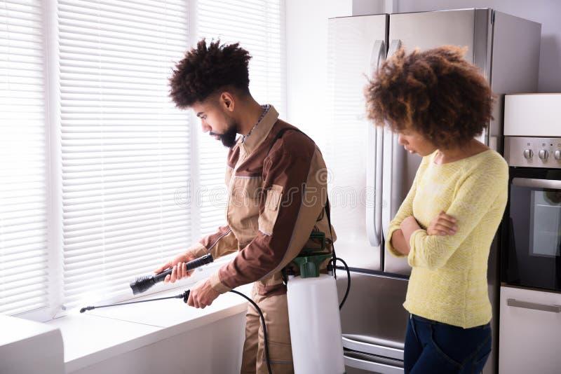 在窗口基石的害虫控制工作者喷洒的杀虫药 免版税库存照片