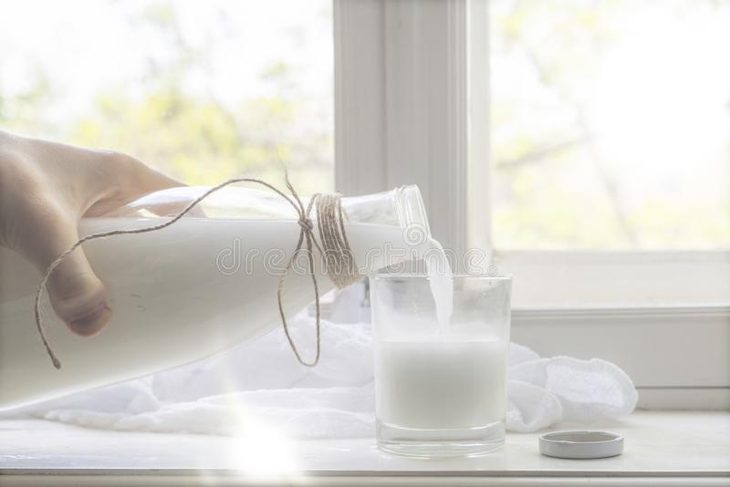 在窗口基石的新鲜的未加工的牛奶,健康早餐在村庄,倒在玻璃的牛奶 库存照片