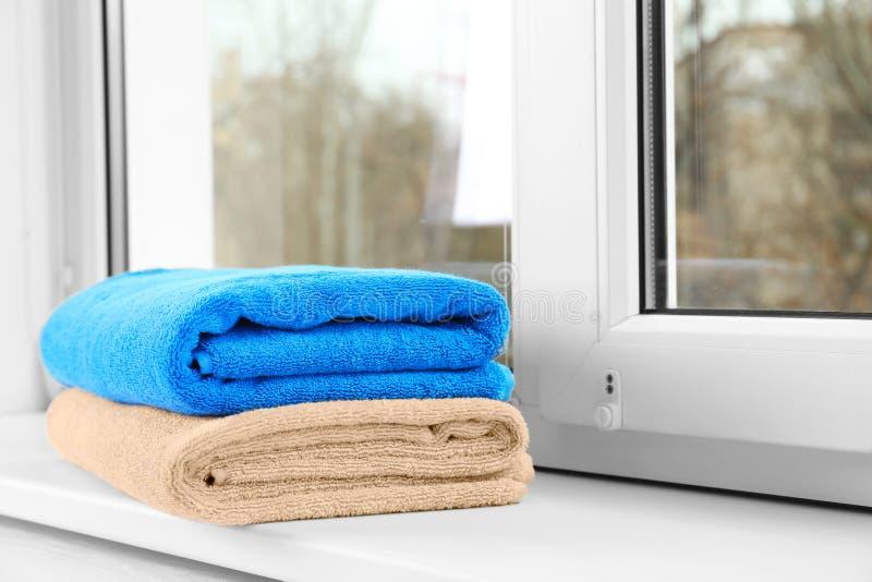 在窗口基石的被折叠的清洁毛巾 免版税图库摄影
