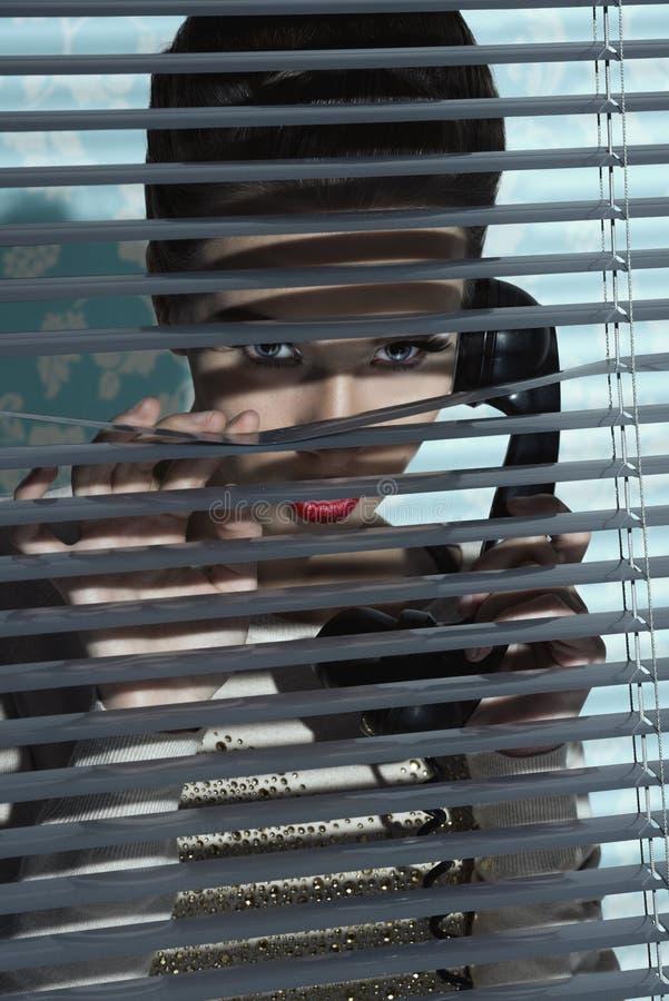 在窗口快门后的迷人的女孩 库存照片