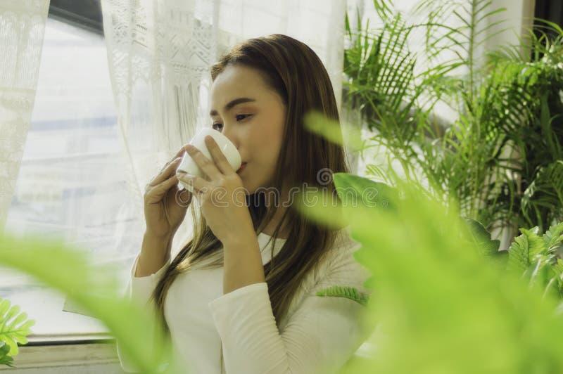 在窗口房子,阳光早晨的美女坐的饮用的咖啡,充满轻松和平安的感觉一个松弛假日 免版税库存照片