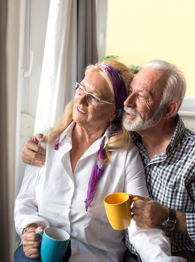 在窗口旁边的年长夫妇 免版税库存图片