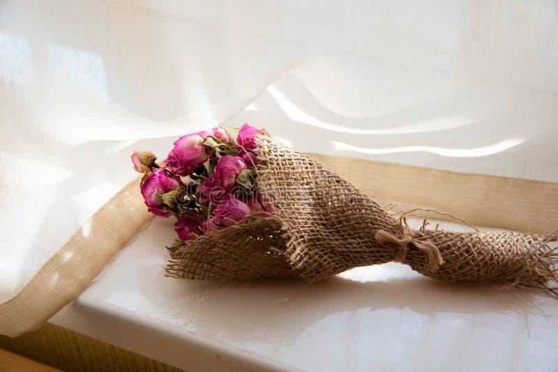 在窗口旁边被安置的干燥花花束 免版税图库摄影