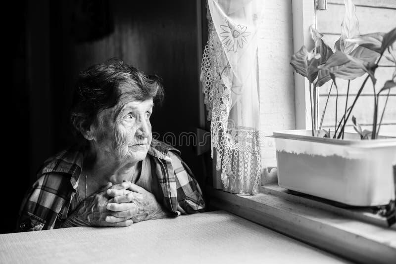 在窗口的一个年长妇女苦思的 免版税图库摄影