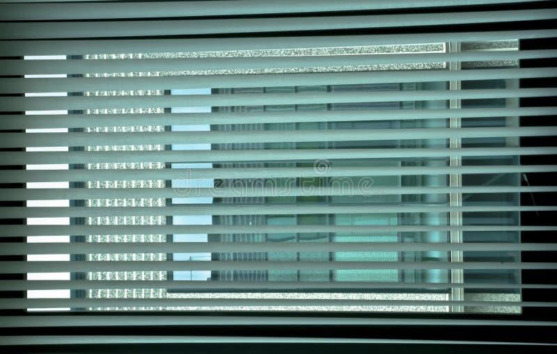 在窗口的几何 在办公室窗口的软百叶帘通过画栅格创造颜色和颜色一场有趣的比赛  库存图片