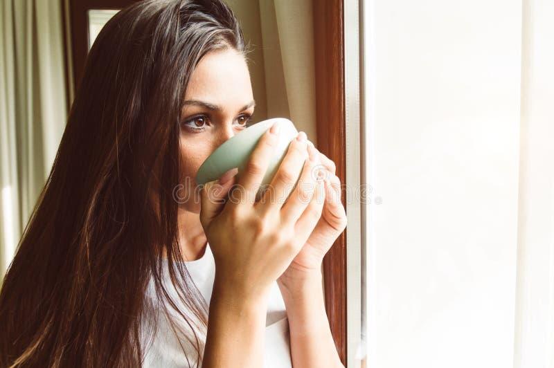 在窗口的妇女想法的饮用的茶 免版税库存图片