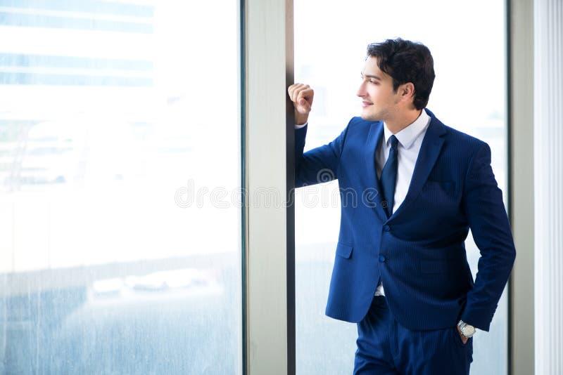 在窗口的年轻英俊的商人身分 免版税库存图片