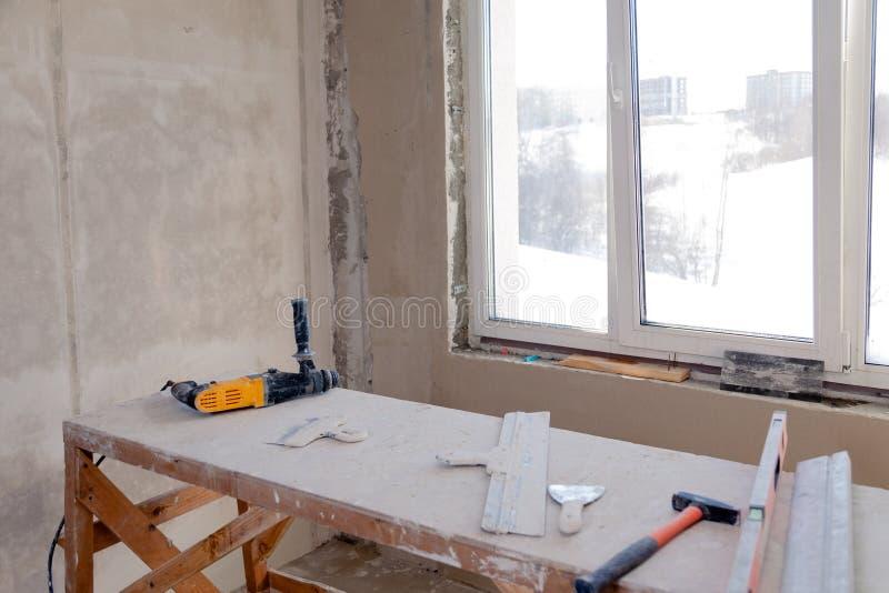 在窗口的木脚手架立场在一间大空的屋子,修理,涂灰泥,绘的墙壁,大厦工具,垃圾 概念 免版税库存照片
