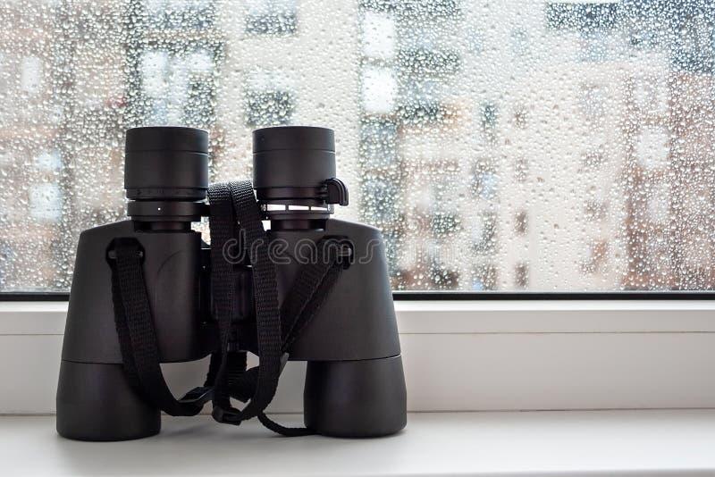 在窗口的白色窗台与在玻璃的雨珠是观察的邻居黑双筒望远镜 免版税库存图片
