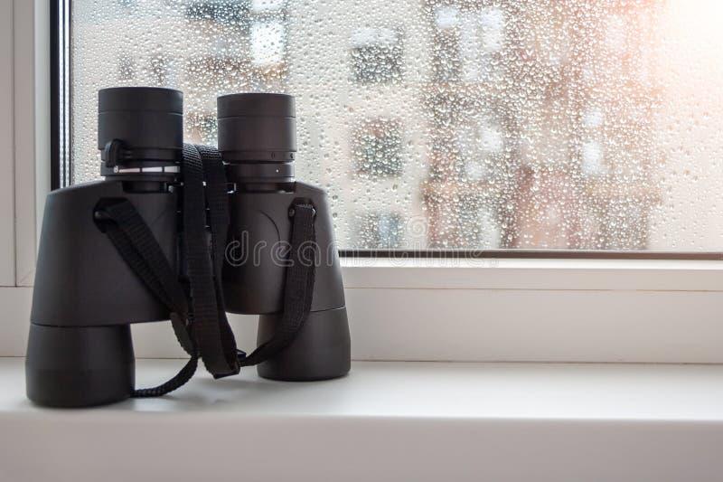 在窗口的白色窗台与在玻璃的雨珠是观察的邻居黑双筒望远镜 免版税库存照片